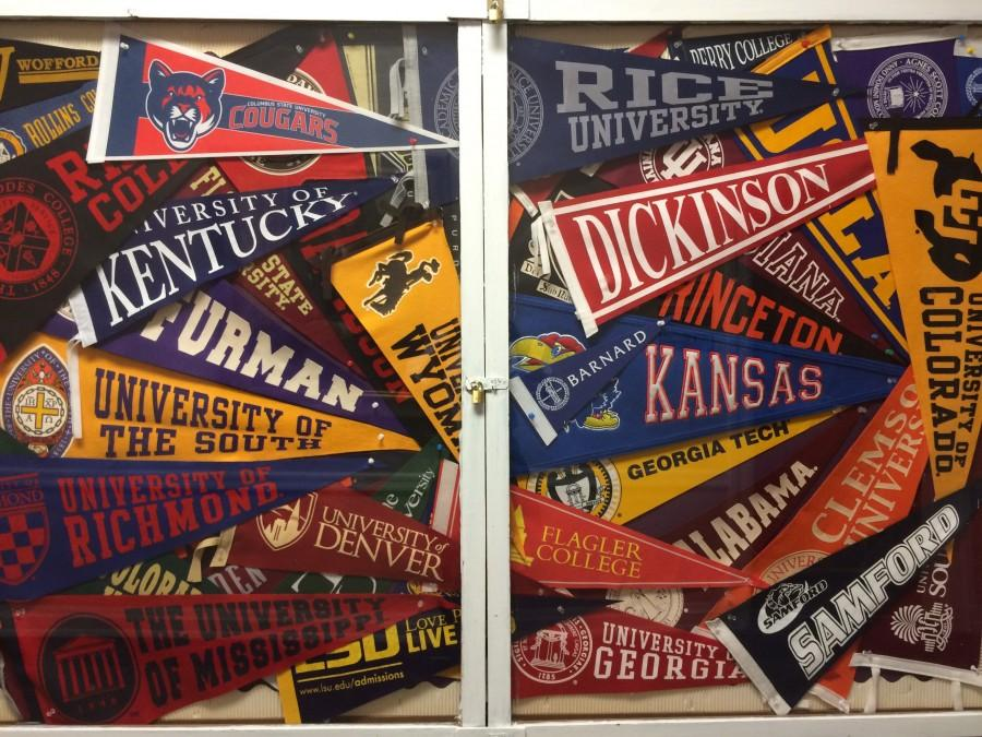 The bulletin board of collegiate flags outside the college guidance office.