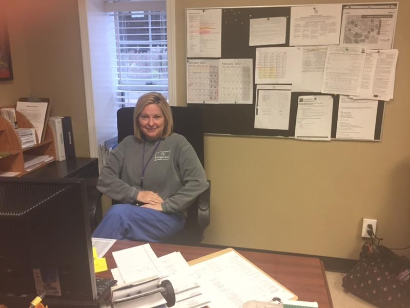 Nurse Kim Hawkins sits at her desk in the health center.