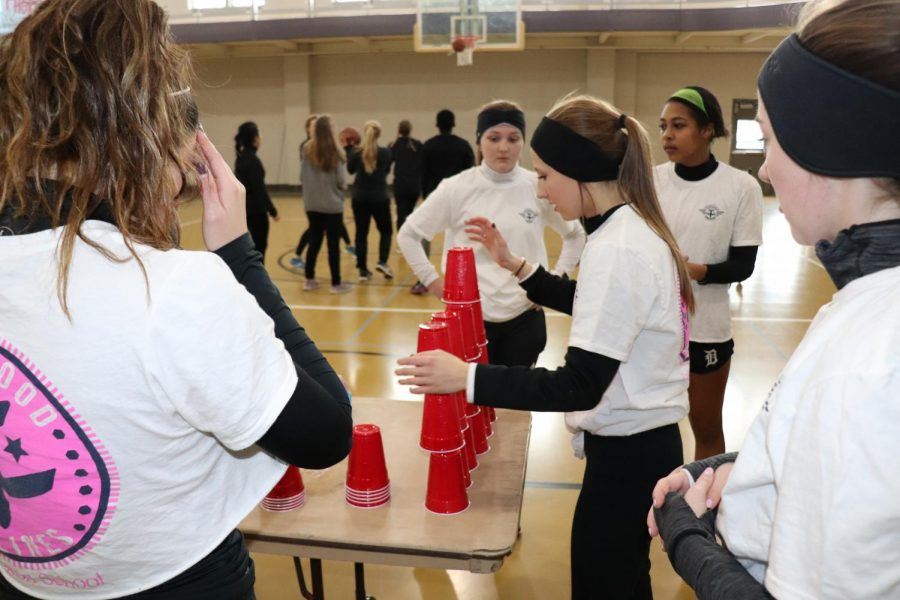 Senior Caroline Cordell stacks cups in a pyramid for Thornwood.