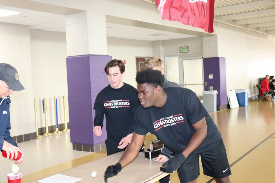 Senior Ethan Willie throws a ping pong ball into cups for Neville.