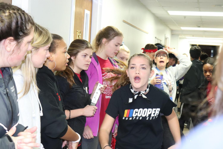 Lauren-Laramier Swann (Cooper) runs through the South Hall hallway cheering.